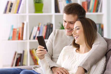 Happy couple watching media content on a smart phone sitting on a couch at home