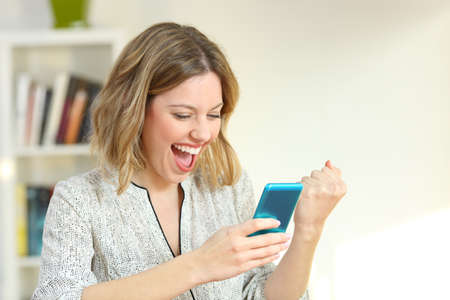 Excited woman reading online smart phone content at home Standard-Bild