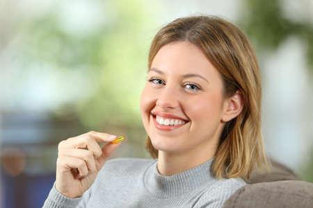 Ritratto di una donna felice che tiene una pillola della vitamina e che esamina macchina fotografica che si siede su uno strato a casa con un fondo verde Archivio Fotografico - 92954102