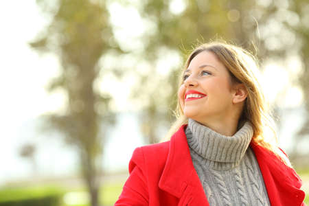 Portrait of a funny woman wearing red jacket looking above outdoors in winter