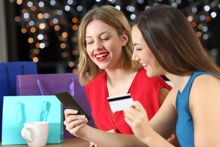 Two fashion shoppers shopping on line with credit card and smart phone in a table at home in the night Stock Photo