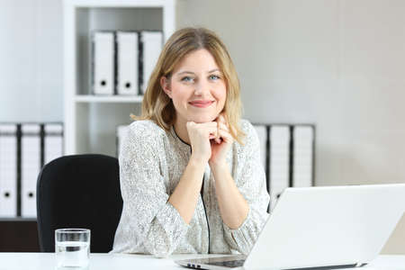 Front view portrait of a businesswoman posing looking at you on a desk at office Stock Photo