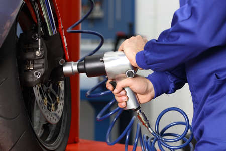 Close up of a motorcycle mechanic hands using a pneumatic gun to loosen a wheel nut in a mechanical workshop