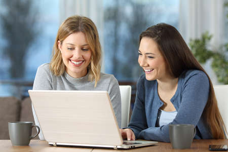 Two happy women watching media content on line in a laptop in a table in the living room at home in the evening Stock Photo
