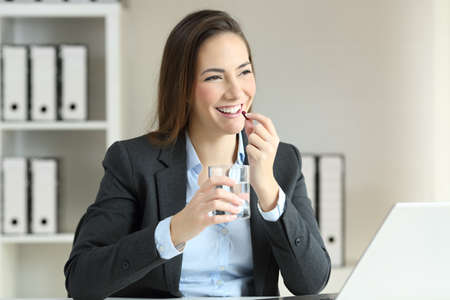 Happy businesswoman taking a pill working at office Stock Photo