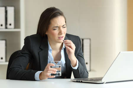 Ill businesswoman complaining and taking pill working sitting in a desktop at office Stock Photo