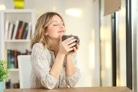 Portrait of a woman breathing and holding a coffee mug at home Фото со стока