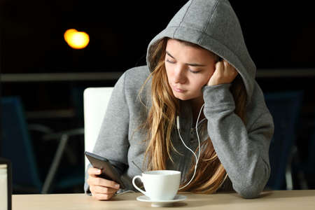 Portrait of a sad teen listening to music with a smart phone and earphones in a coffee shop in the night