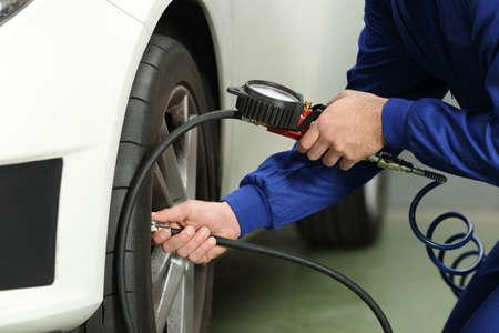Gros plan d'un mécanicien de voiture vérifiant l'air des pneus avec un manomètre