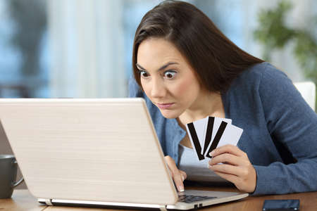 Obsessed compulsive on line shopper or gambler checking results in a laptop at home