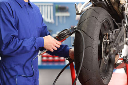 Close up of a motorbike mechanic hand checking tires air with a pressure gauge in a workshop 스톡 콘텐츠