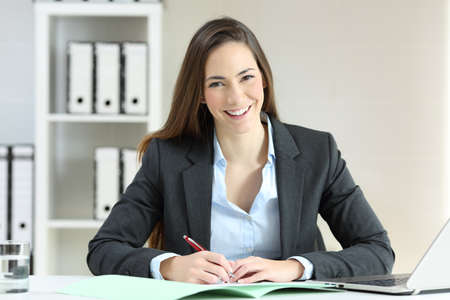 Front view portrait of an office worker writing in documents posing looking at camera