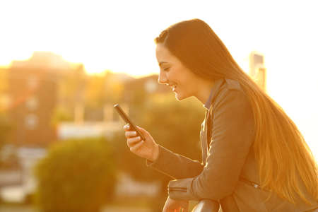 Side view portrait of a happy girl using a smart phone outdoors in a house balcony at sunset Stock Photo