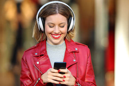Front view portrait of a fashion blonde girl listening music wearing headphones on the street with a storefront in the background Stock Photo
