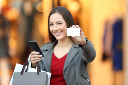 Potrait of a fashion shopper showing credit card and phone in a mall Standard-Bild