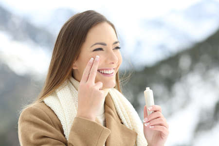 Portrait of a beauty happy lady applying facial moisturizer cream in winter