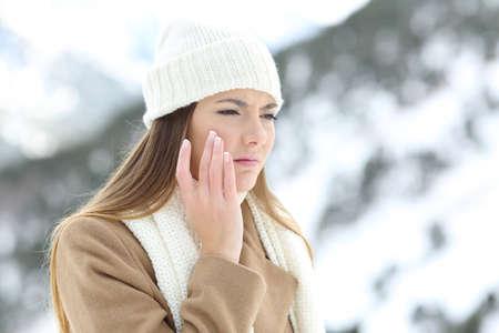Verärgerte Frau, die eine Skifahrenschutz-Feuchtigkeitscremecreme im Winter in einem schneebedeckten Berg verwendet