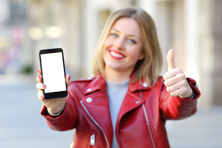 Front view of a fashion happy woman showing a smartphone blank screen with thumbs up on the street Stock Photo