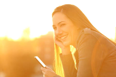 Happy girl holding a smartphone looking at you outdoors at sunset