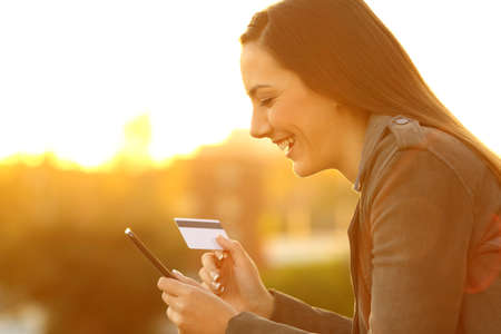Side view portrait of a smiley girl buying on line with credit card and smart phone in a balcony at sunset