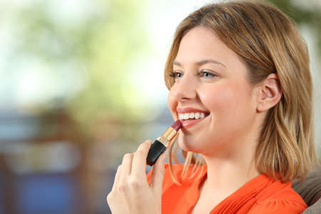 Portrait of a woman applying a lipstick painting lips at home Stock Photo