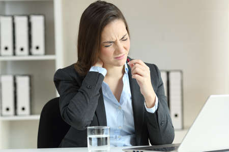 Businesswoman suffering neck ache and taking a pill at office