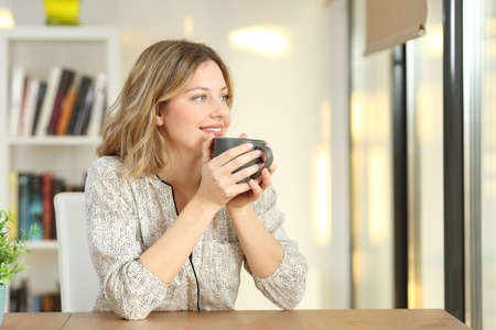 Portrait of a woman looking through a window drinking coffee sitting in a table at home Standard-Bild