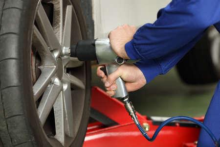 Cerca de las manos de un mecánico de automóviles aflojar las tuercas de la rueda con una pistola neumática en un taller mecánico