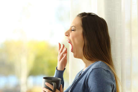 Side view portrait of a woman yawning in the morning at home