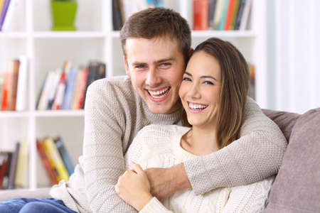 Front view portrait of a happy couple with perfect smile looking at you sititng on a couch in the living room at home in winter Stock Photo