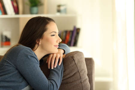 Side view portrair of a satisfied pensive woman looking through a window sitting on a couch in the living room at home