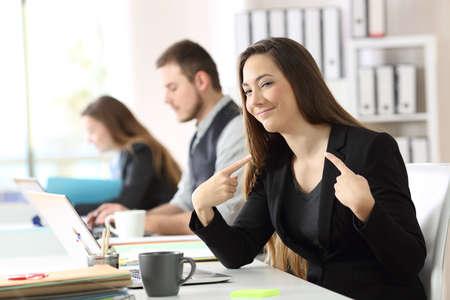 Porträt einer stolzen Geschäftsfrau, die mit beiden Zeigefingern in einem Schreibtisch im Büro sich zeigt