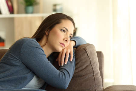 Sad woman looking trough a window sitting on a couch in the living room at home Stockfoto