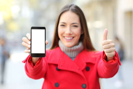 Front view portrait of a happy woman showing a smart phone blank screen in winter on the street