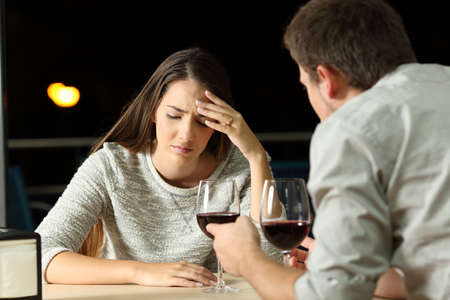 Sad couple arguing during a bad date in a restaurant in the night
