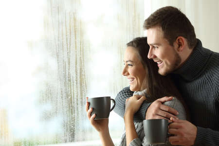 Side view portrait of a happy couple holding coffee mugs looking outside through a window a rainy day of winter at home Stockfoto
