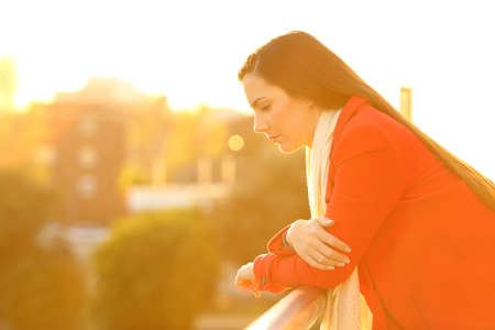 Side view portrait of a sad pensive woman looking down in a balcony at sunset in winter