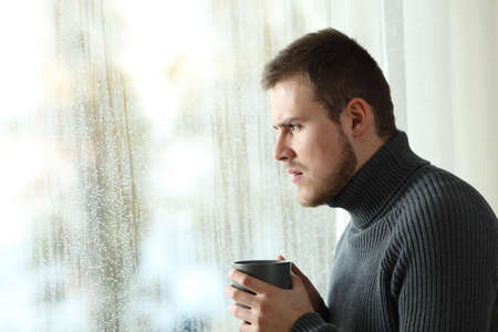 Side view portrait of an angry man looking outdoors through a window in a rainy day of winter at home Stock Photo