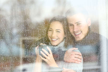 Front view portrait of a positive couple looking outdoors through a window in a rainy day of winter at home