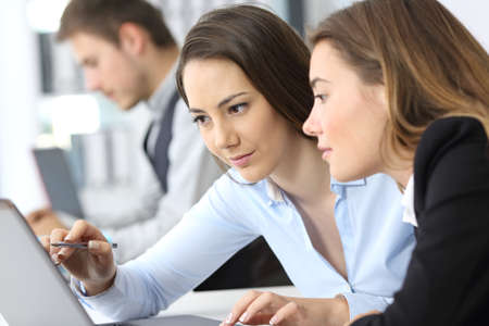 Two businesswomen working on line together with a laptop at office Stock Photo - 93219508