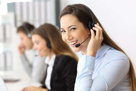 Portrait of a happy telemarketer working looking at you at call center Stock Photo