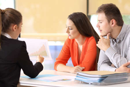 Three businesspeople analyzing a growth graph at office