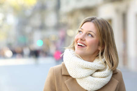 Portrait of a happy woman looking at side on the street in winter