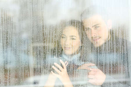 Satisfied couple looking through a window at home in a rainy day