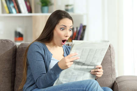 Portrait of a surprised woman reading amazing news in a newspaper sitting on a couch in the living room at home Stockfoto