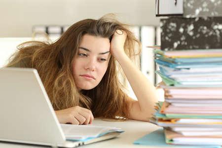 Moe en verveeld stagiair kijken naar de hoeveelheid papierwerk op kantoor