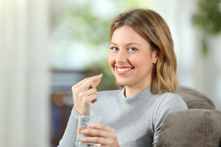 Happy woman posing looking at camera holding a vitamin pill ready to take it sitting on a couch in the living room at home
