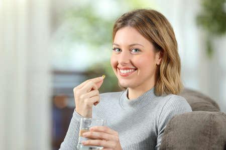 Donna felice che posa esaminando macchina fotografica che giudica una pillola della vitamina pronta a prenderla sedendosi su uno strato nel salone a casa