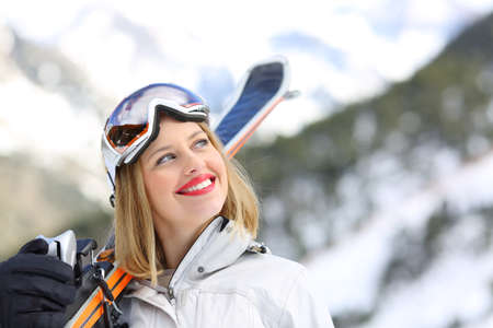 Satisfied skier holding skies on winter holidays  looking at side in a snowy mountain