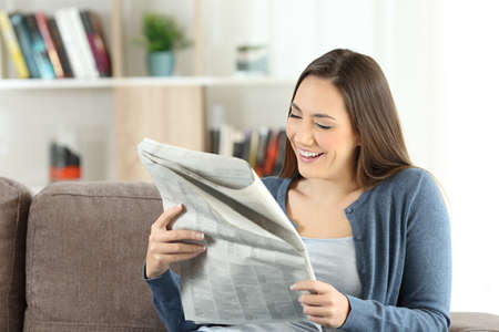 Happy lady reading a newspaper sitting on a couch in the living room at home